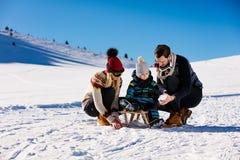 父母身分、时尚、季节和人概念-有雪撬的走在冬天的孩子的愉快的家庭户外 图库摄影