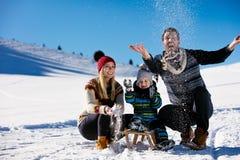 父母身分、时尚、季节和人概念-有雪撬的走在冬天的孩子的愉快的家庭户外 免版税库存照片