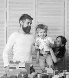 父母身分概念 一起花费时间的年轻家庭在游戏室 免版税库存照片