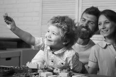 父母身分概念 与微笑的面孔的孩子在塑料砖附近 免版税库存照片