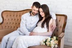 父母身分概念-坐年轻美好的怀孕的夫妇  免版税库存图片