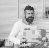 父母身分概念 有胡子和髭的人拿着建筑 免版税图库摄影