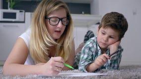 父母身分,有儿童凹道图片的妈妈与在说谎在地板上的白色板料的色的铅笔户内周末 股票视频