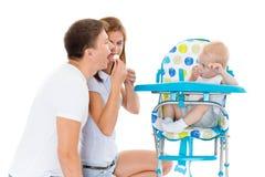 年轻父母饲料婴孩。 免版税图库摄影