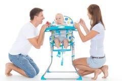 年轻父母饲料婴孩 图库摄影