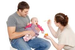 年轻父母饲料婴孩 免版税库存图片