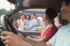 父母驾驶和说好海湾对儿子和祖父母 免版税库存照片