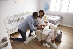 父母从有新出生的婴孩的医院回家在托儿所 免版税库存图片