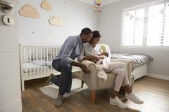 父母从有新出生的婴孩的医院回家在托儿所 免版税库存照片