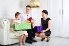 父母给礼物小女儿在沙发 免版税库存图片