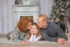年轻父母画象在圣诞树附近亲吻他们的地毯的女儿 库存照片