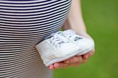父项 预期婴孩的愉快的年轻夫妇 与I的婴孩袜子爱妈妈,并且我爱在他们写的爸爸 免版税图库摄影