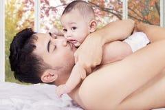 爸爸亲吻他逗人喜爱的儿子在家 库存图片