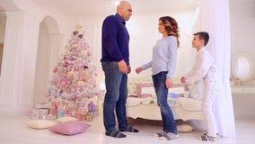 爸爸人做笔记给儿子,女性母亲为孩子调解在明亮的卧室圣诞树和礼物 股票视频