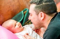 爸爸做面孔做鬼脸的新出生的婴孩笑 免版税库存照片