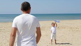 幸福家庭:使用由海的父亲和儿子 爸爸发射玩具飞机对边,站立在孩子旁边 ?treadled 股票录像