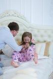 爸爸发痒女儿,在家演奏与在床上的女孩 库存图片
