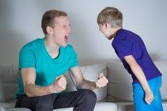爸爸叫喊对他的儿子 免版税库存照片