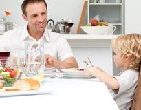 爸爸吃愉快他查找的意大利面食儿子 免版税库存图片