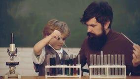 爸爸和他的使用试管的小儿子老师和男小学生在类 人与学龄前儿童孩子的老师戏剧 ?? 影视素材