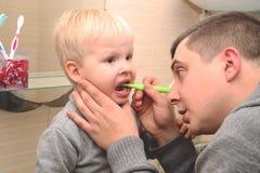 爸爸和儿子在卫生间里刷他们的牙 对孩子的父亲掠过的牙 库存图片