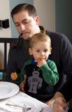 爸爸和儿子在饭桌上 免版税库存照片