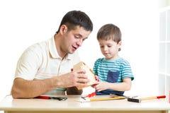 爸爸和儿子孩子与大厦工具一起使用 免版税库存照片
