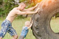 爸爸和儿子推挤一个大轮胎 街道锻炼 库存照片
