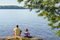 爸爸和儿子湖边钓鱼 库存照片