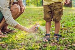 爸爸和儿子用途蚊子浪花 在室外的皮肤的喷洒的杀虫剂 库存图片