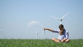 爸爸和儿子看在距离的一次鸟飞行,以造风机为背景的射击 股票视频