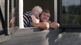 爸爸和儿子看窗口并且摇他们的手 影视素材