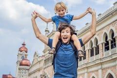 爸爸和儿子苏丹阿卜杜勒萨玛德大厦背景的在吉隆坡,马来西亚 旅行与儿童概念 免版税库存照片
