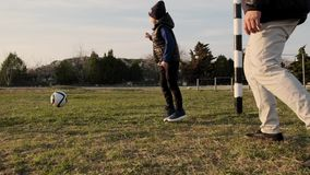 爸爸和儿子获得踢足球的乐趣户外在日落慢动作的春天 股票视频