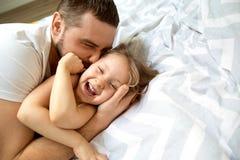 爸爸和女儿在家获得乐趣在床上 日父亲s 免版税库存照片