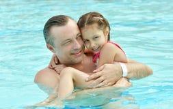 爸爸和女儿在水池放松 图库摄影