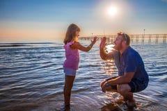 爸爸和女儿由海互相给五 免版税库存照片