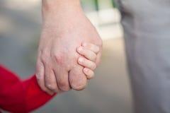 爸爸和女儿的手 免版税库存照片
