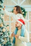 爸爸和女儿装饰圣诞树户内 在Xmas前的早晨 免版税库存照片
