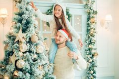 爸爸和女儿装饰圣诞树户内 在Xmas前的早晨 库存图片