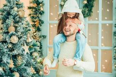 爸爸和女儿装饰圣诞树户内 在Xmas前的早晨 免版税图库摄影