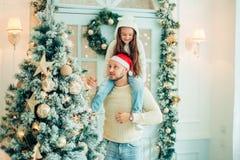 爸爸和女儿装饰圣诞树户内 在Xmas前的早晨 免版税库存图片