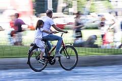 爸爸和女儿骑自行车(摇摄作用) 免版税库存照片
