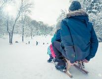 爸爸和孩子在冬天雪的Sledging 免版税库存照片