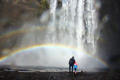 爸爸和孩子在彩虹下在Skogafoss重的瀑布的脚在冰岛 免版税库存照片