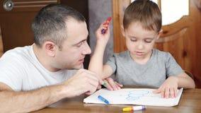 爸爸和孩子在明亮的颜色蜡笔或铅笔的纸在家坐在桌上在假日期间并且画 节假日 影视素材