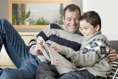 爸爸和孩子读取杂志 免版税库存图片