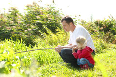 爸爸和小女儿在湖附近 图库摄影