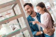 爸爸和小女儿选择在咖啡馆的一个蛋糕 库存图片