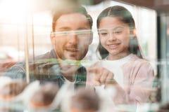 爸爸和小女儿选择在咖啡馆的一个蛋糕 免版税库存图片